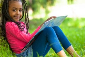 young girl reading outside