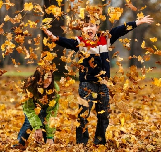 Children throwing fall leaves
