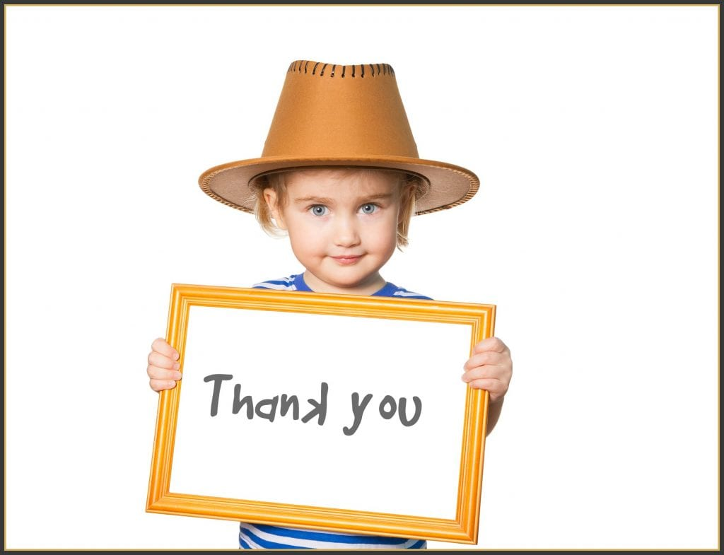 child holding hand written thank you sign