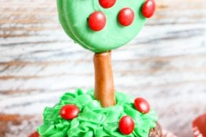 cupcake with an apple tree made of green dipped oreos and red m & m