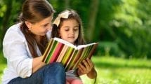 Happy family reading book at park